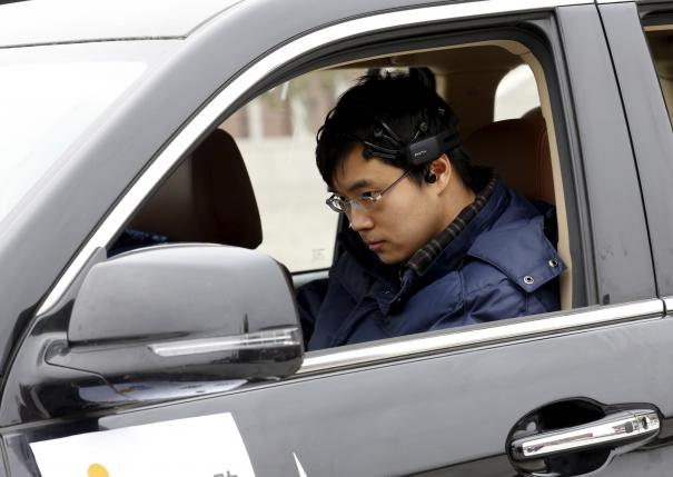 Researcher Zhang Zhao wearing a brain signal-reading equipment prepares to move a car with his brain wave, during a demonstration at Nankai University in Tianjin